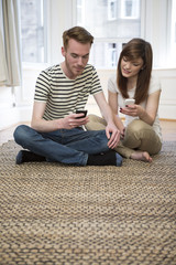 Young couple sitting on floor at home using smartphone.