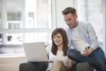 Couple relaxing together in sofa with laptop pc.