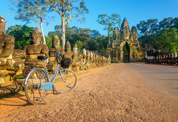 Classic bicycle on road and North Gate of Angkor Wat, Cambodia