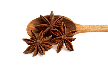 Star anise in wooden spoon, isolated on a white background