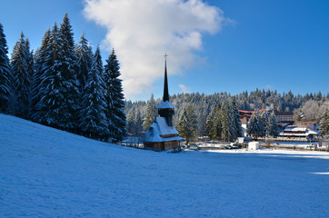 Landscape in winter, with forest and church, in Romania