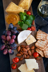 Cheese, wine, crackers board platter spread with grapes nuts