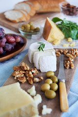 Selection of cheese for party with olives grapes bread