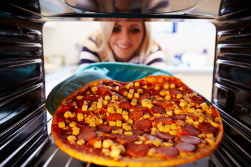 Woman Putting Pepperoni Pizza Into Oven To Cook