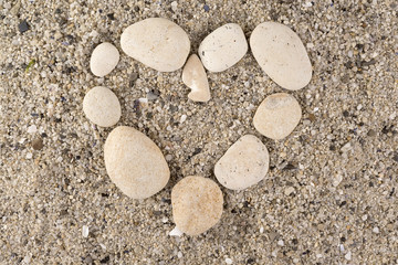 stones in shape of heart on sea sand