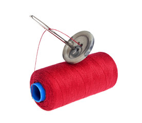 Needle, button and colored bobbin of lurex thread isolated on wh