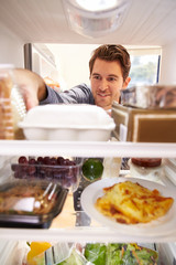 Man Looking Inside Fridge Filled With Food