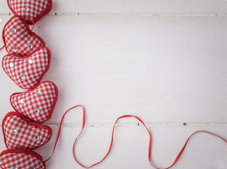 red check hearts on rustic white wooden background