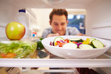 Man Looking Inside Fridge Full Of Food And Choosing Salad