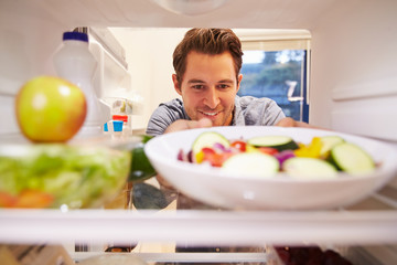 Man Looking Inside Fridge Full Of Food And Choosing Salad