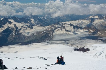 Two alpinists looking at mountain ridge
