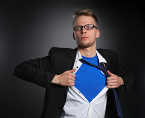 Young businessman acting like a super hero and tearing his shirt
