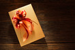 Gift box with ribbon on old wooden background