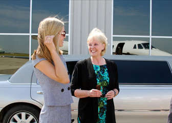 Two ladies chatting standing by limo