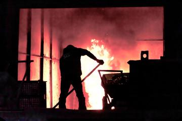 Man is working in the splashing molten iron - Stock Image