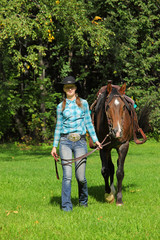 Cute smiling cowgirl in hat with a saddle horse