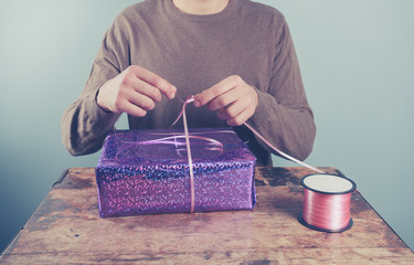 Man at table wrapping presents