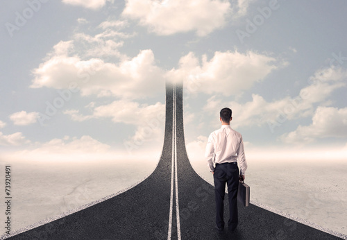 Businessman looking at 3d road that goes up in the sky - 73920491