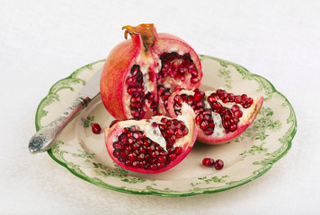 Opened red pomegranate on a rustic plate