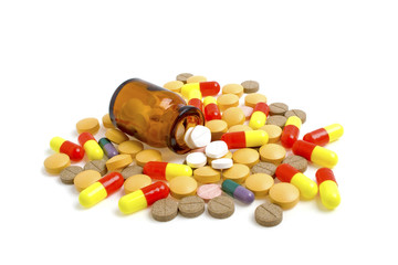 Colored pills, tablets and bottle on a white background