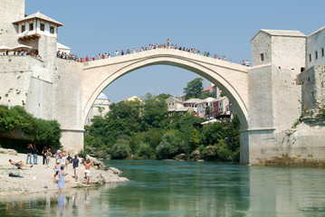 Tourists watching at people who jump from the bridge of Mostar