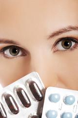 Close up woman holding pills