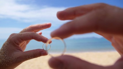 Wedding Rings in Groom and Bride Hands on the Beach.