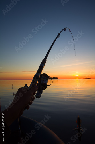 Sunset river perch fishing with the boat and a rod - 73923239