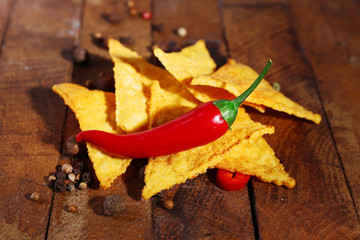 Tasty nachos and chili pepper on wooden background