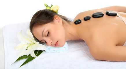 Beautiful young woman in spa salon with spa stones