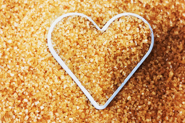 heart filled with brown cane sugar, food background