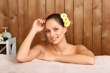 Beautiful young woman in spa salon on wooden wall background