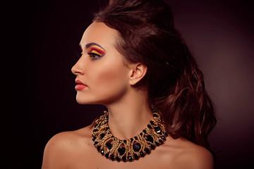 Fashion portrait of brown-eyes  woman.Gold jewelry. Orange yello