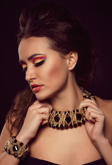 Fashion portrait of brown-eyes  woman.Gold jewelry. Orange yello