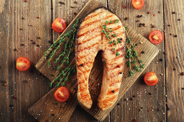 Grilled salmon on cutting board on wooden background