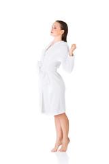 Side view woman standing, wearing bathrobe