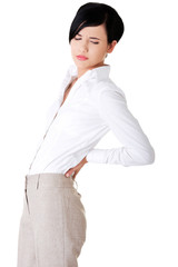 Attractive businesswoman suffers from back pain