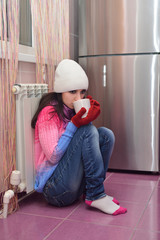 Girl sitting on the floor next to a radiator and drinking tea