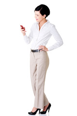 Full length business woman using mobile phone