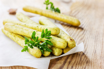 Bread sticks with parsley and garlic on a wooden table