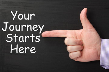 Finger pointing at Your Journey Starts Here on a blackboard