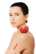 Side view bare brunette with red apple on shoulder