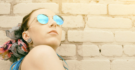 portrait young active girl of the hipster outdoors in sunglasses