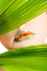 Woman with an artistic makeup behind a leaf