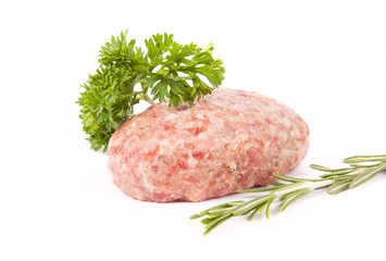 raw meat cutlet with a sprig of parsley and rosemary on a white
