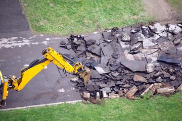 Heavy road construction machine breaks up old asphalt