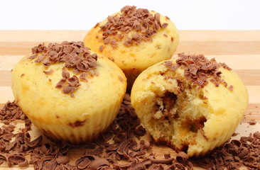 Fresh baked muffins and grated chocolate on wooden cutting board