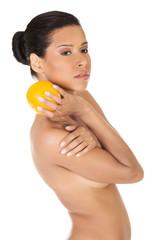 Slim nude woman holding an orange