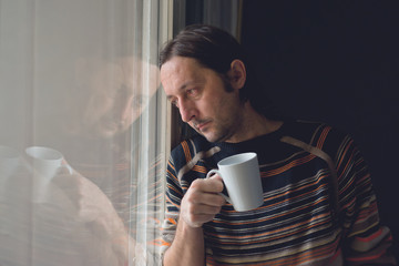 Sad man by the window drinking coffee