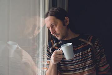 Sad man by the window drinking coffee